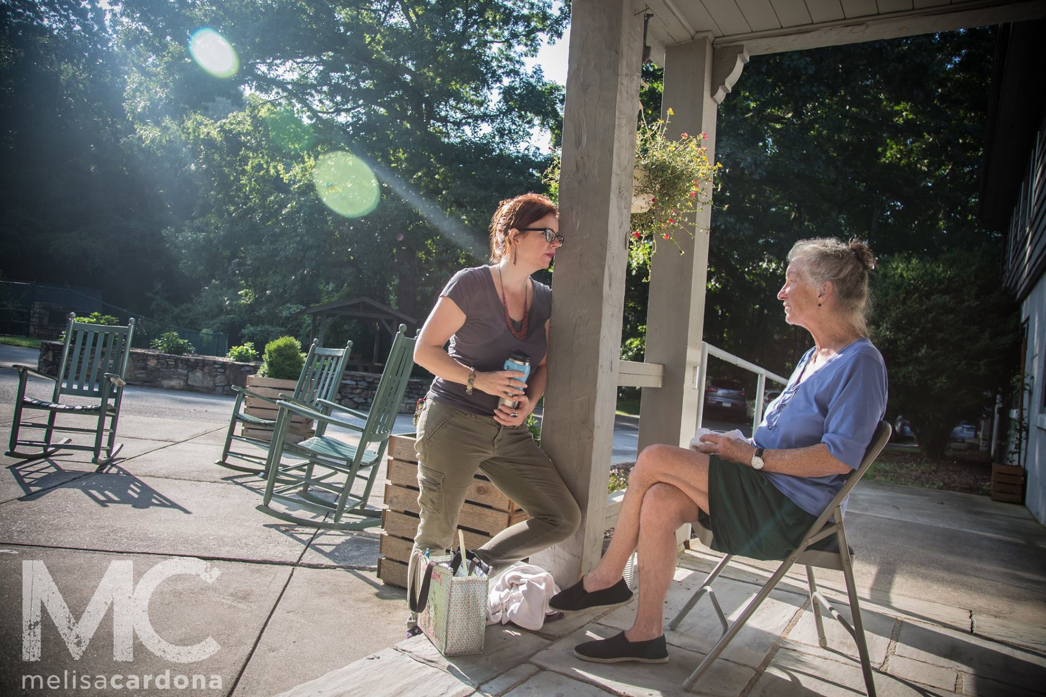 Two women of different generations sit on a porch talking to each other, the morning sun warms them from behind