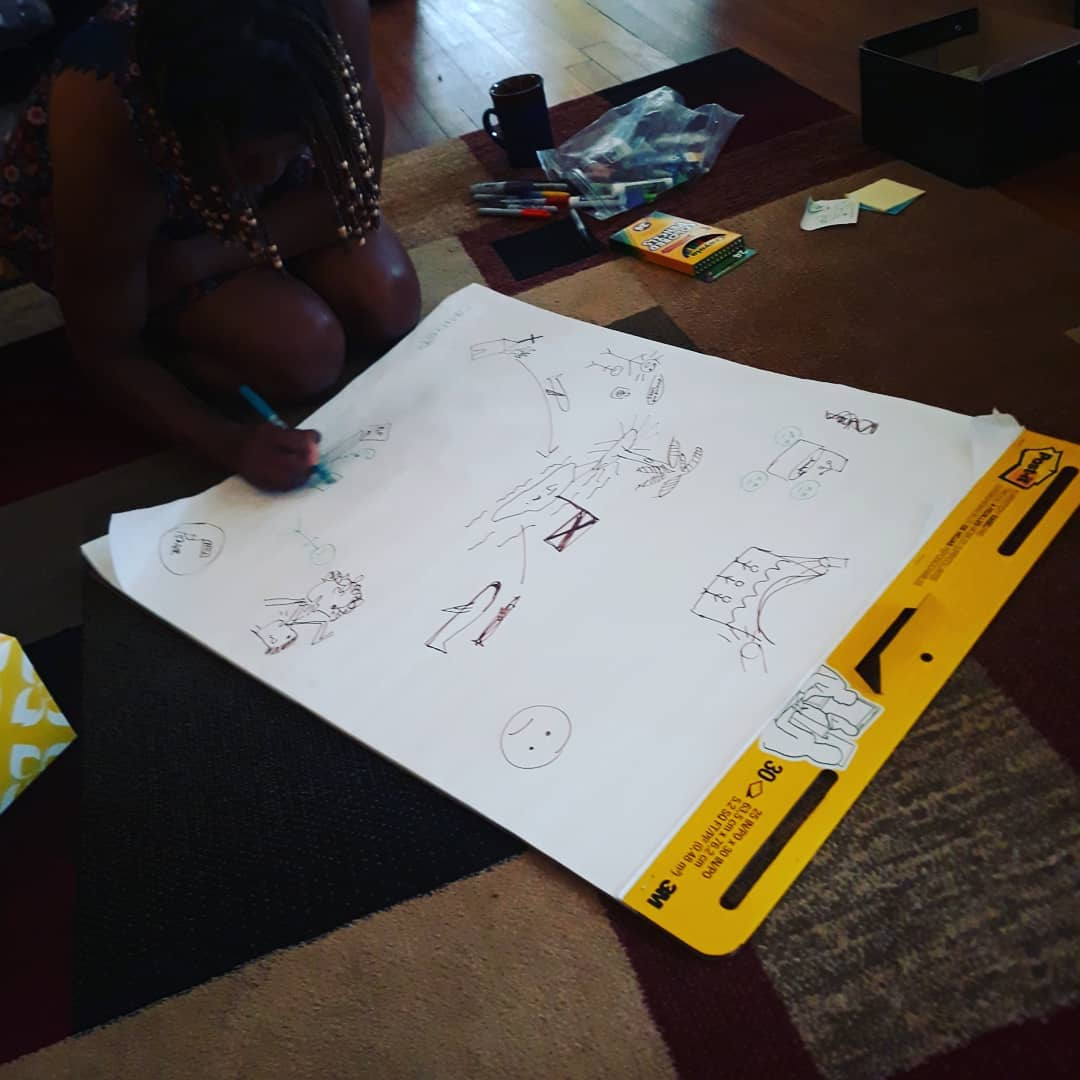a Black woman sits on the floor drawing on a large piece of paper with multiple markers