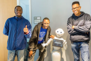 Three young Black men stand with smiles and thumbs up next to a small white robot that's also smiling