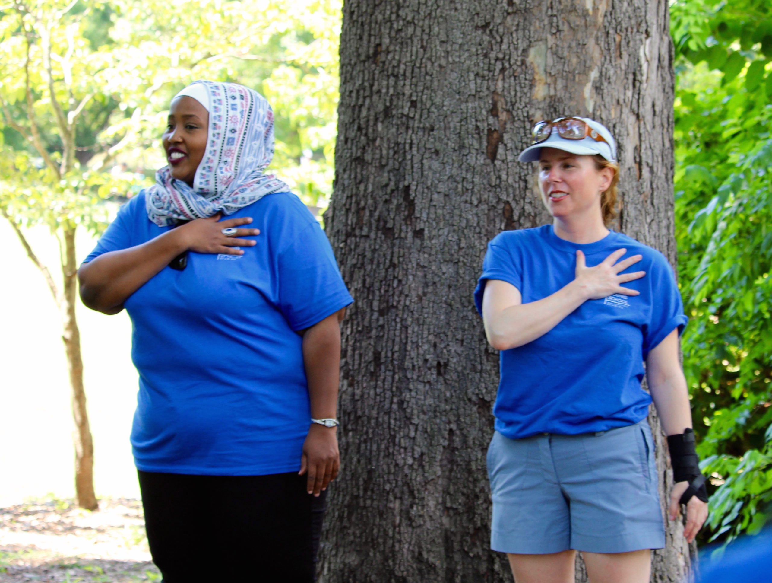 an African woman with a headscarf and a white woman wearing a ball cap are both crossing their hearts, each are wearing blue t-shirts