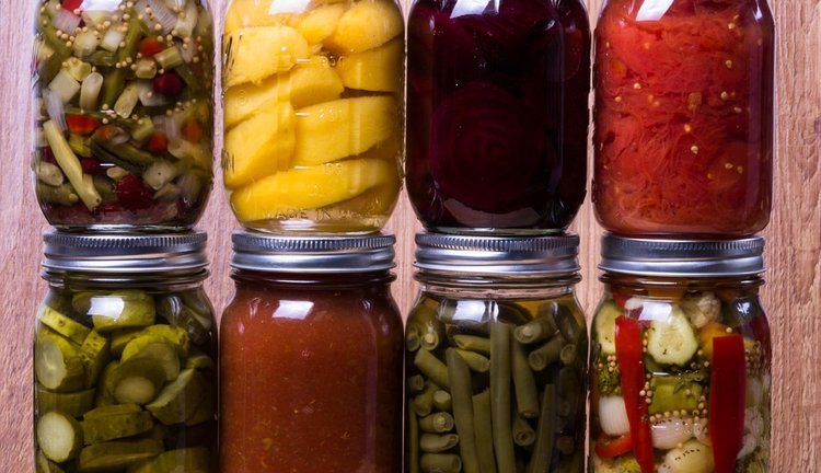 a collection of mason jars with various home canned goods inside