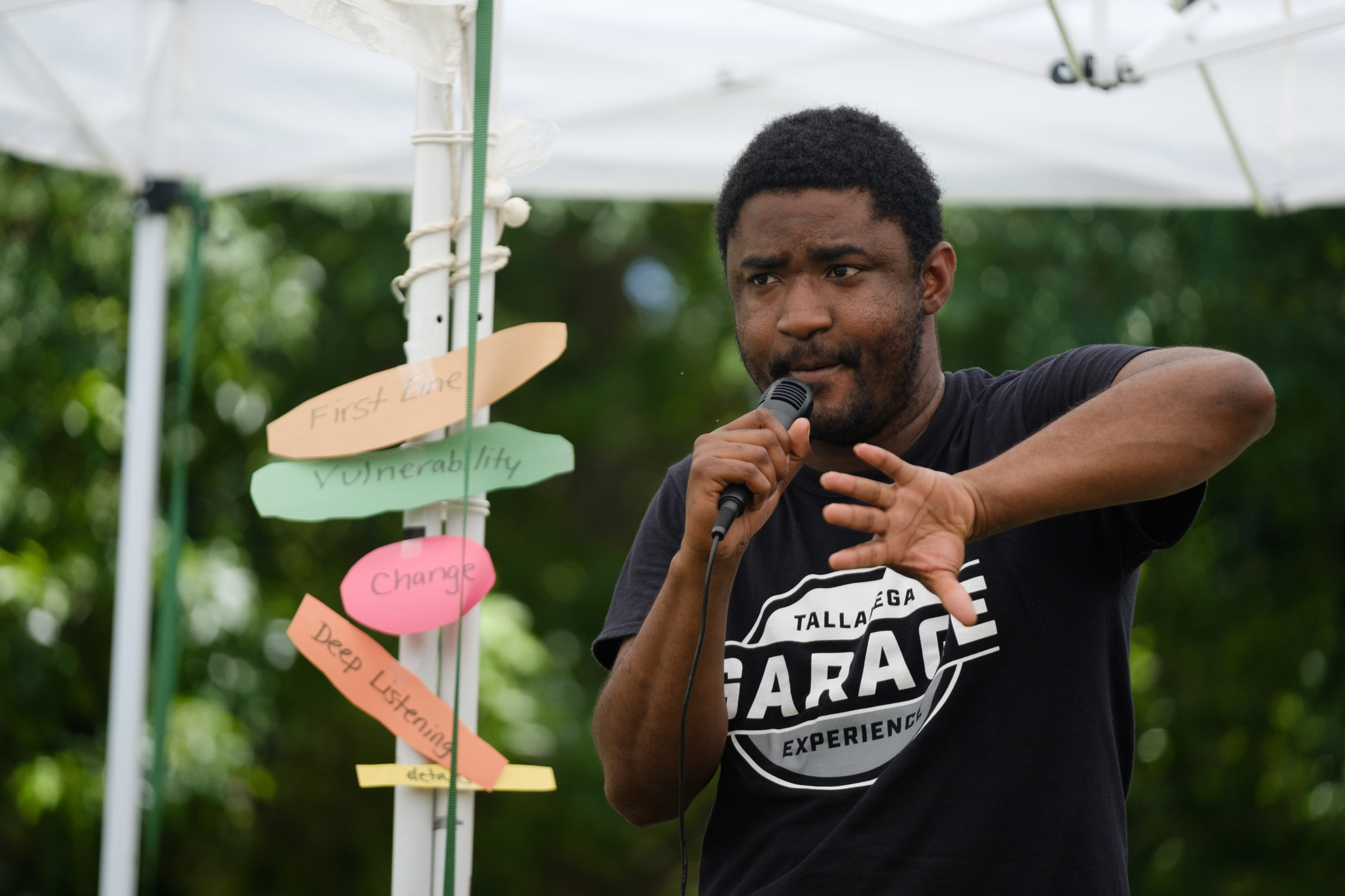 a young black man speaks into a microphone while gesturing with his hands