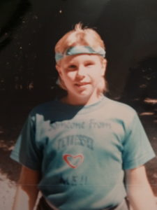 a young white girl has a bandana tied around her head a tight t-shirt in an old photograph from the 1980s